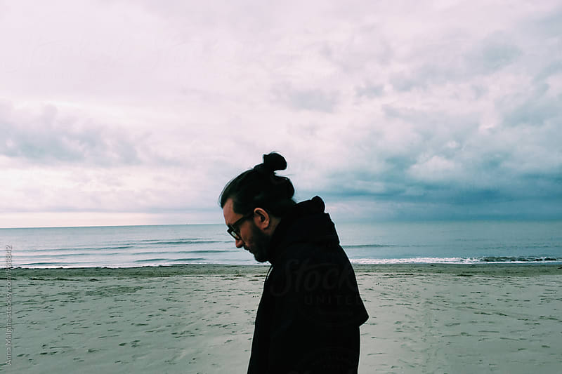 A portrait of a man in front of sea by Anna Malgina for Stocksy United