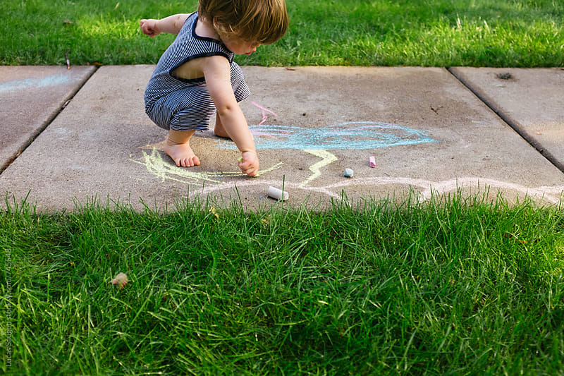 A young boy draws with chalks outside in the summer. by Lucas Saugen for Stocksy United