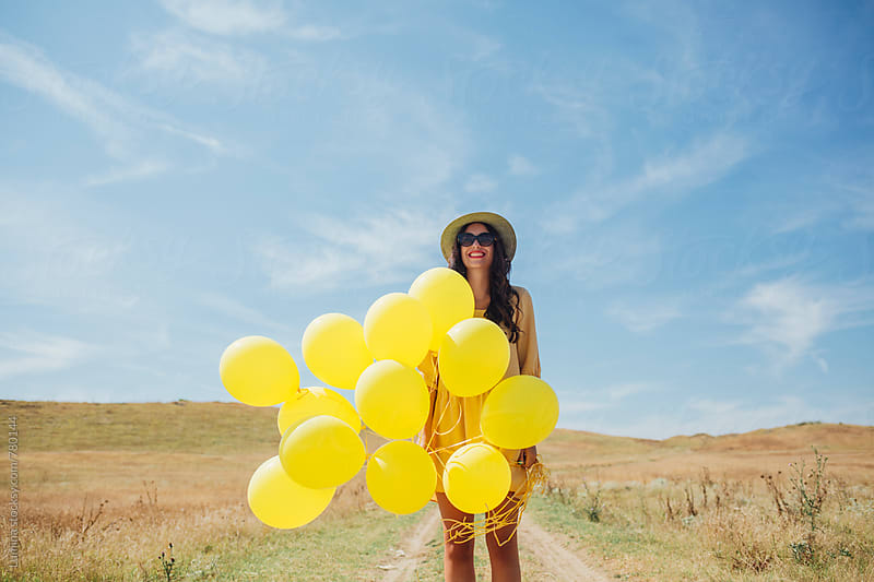 Pretty Woman Holding Yellow Balloons by Lumina for Stocksy United