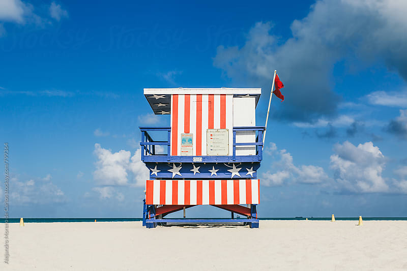 Lifeguard hut with United States flag decoration in South Beach, Miami by Alejandro Moreno de Carlos for Stocksy United
