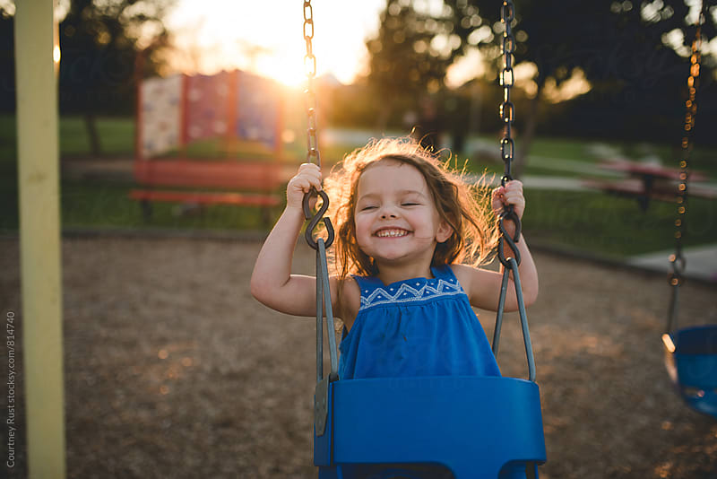 swinging in the setting sun  by Courtney Rust for Stocksy United