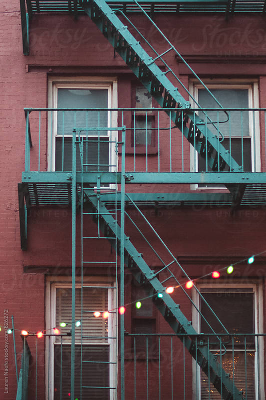 Colored lights hanging from fire escape  by Lauren Naefe for Stocksy United
