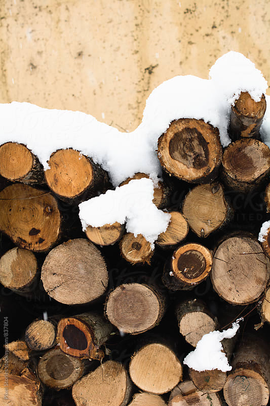 Stacked firewood covered with snow by Pixel Stories for Stocksy United