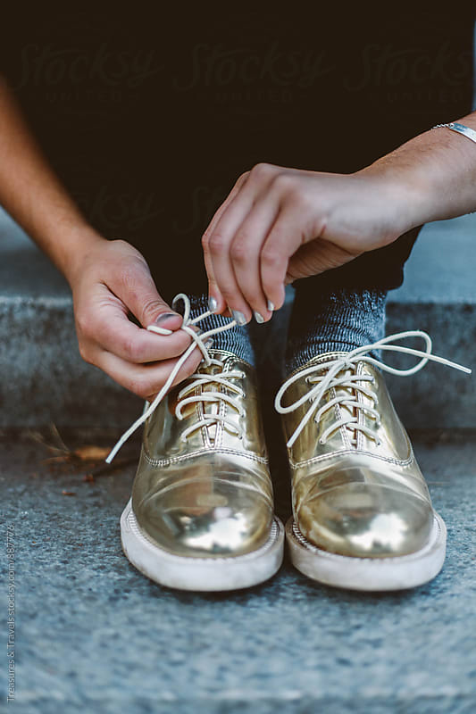 Woman Tying Gold Shoes by Treasures & Travels for Stocksy United
