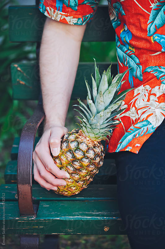 Man in hawaiian shirt sitting on bench with a fresh pineapple by Emoke Szabo for Stocksy United