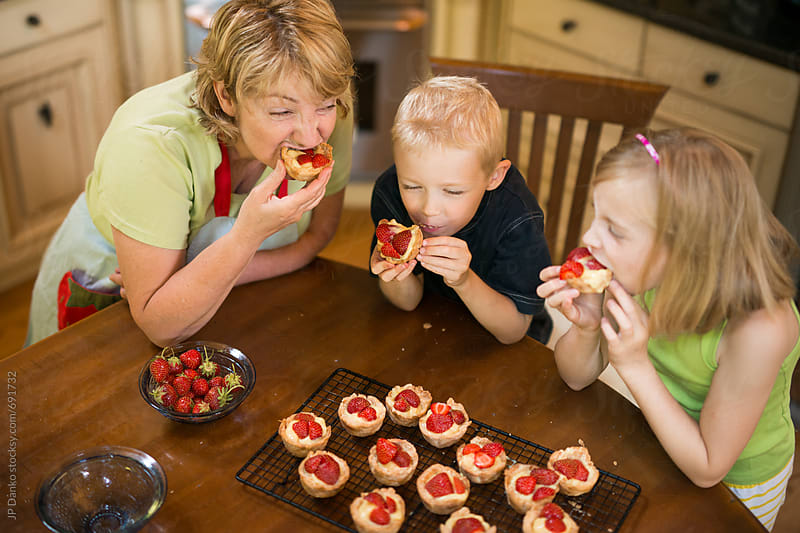 Grandmother and Grandchildren Eating Pastry Custard and Strawberry Tarts from Scratch Together by JP Danko for Stocksy United