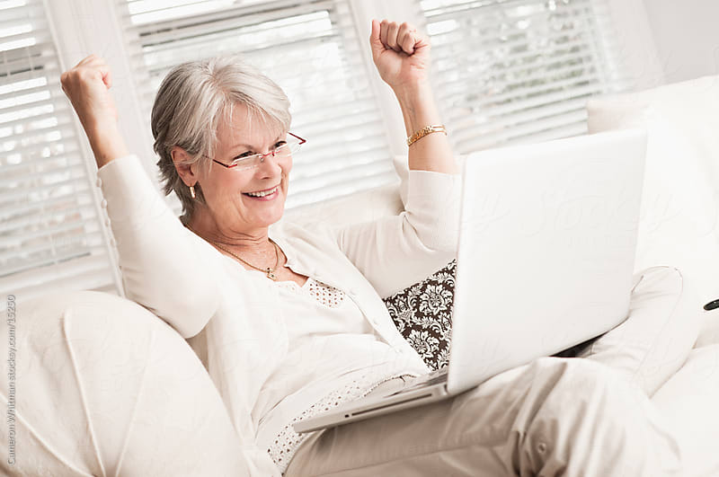 Mature Woman Celebrating With Her Laptop by Cameron Whitman for Stocksy United