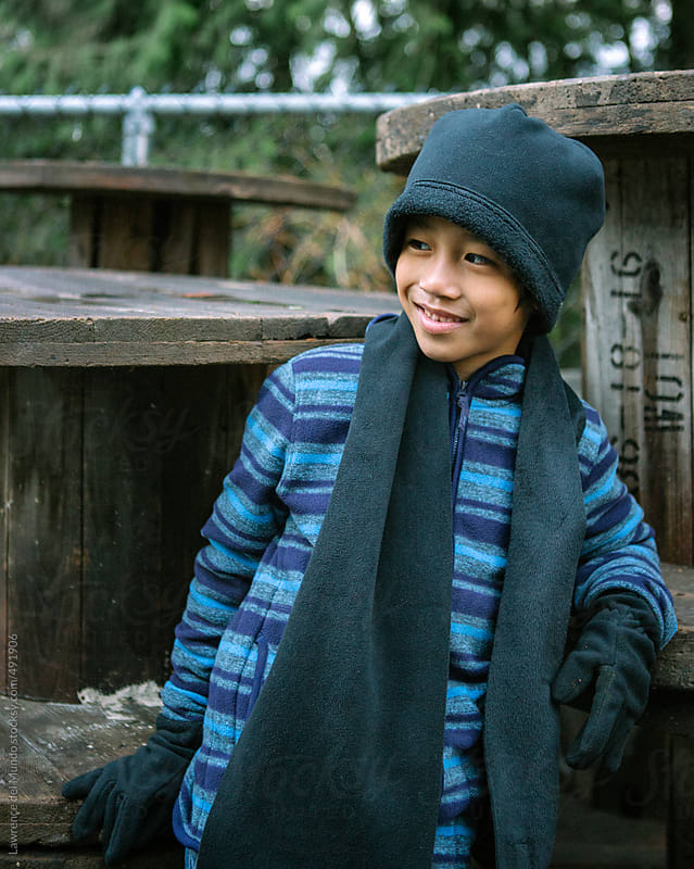 Asian boy in winter clothes smiling  by Lawrence del Mundo for Stocksy United