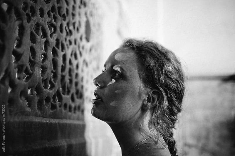 A young woman gazes through a carved screen in a historical building.  by Julia Forsman for Stocksy United