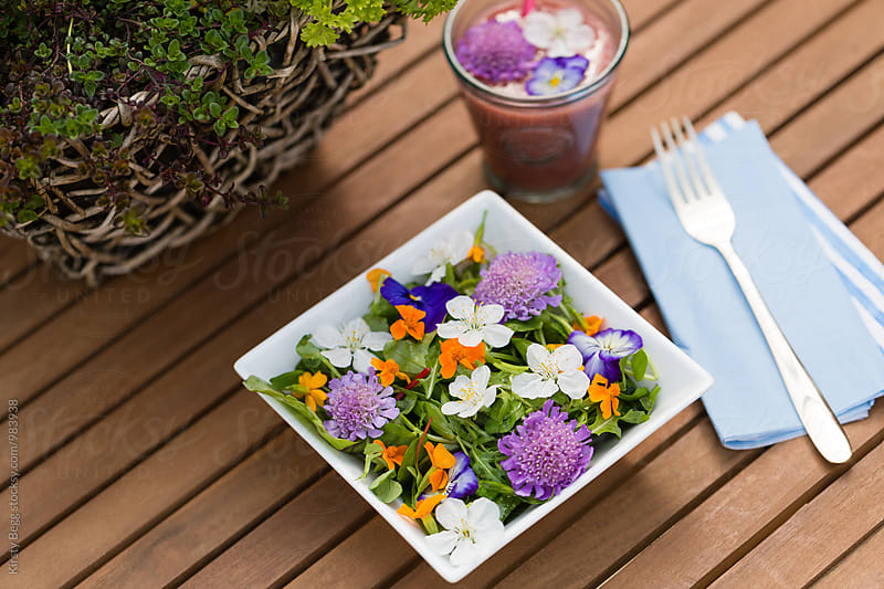 Horizontal shot of salad outside with flower garnish by Kirsty Begg for Stocksy United