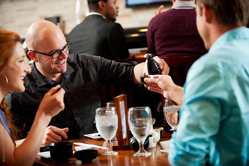 Sushi: Guy Tops Off Friend's Sake Cup by Sean Locke for Stocksy United
