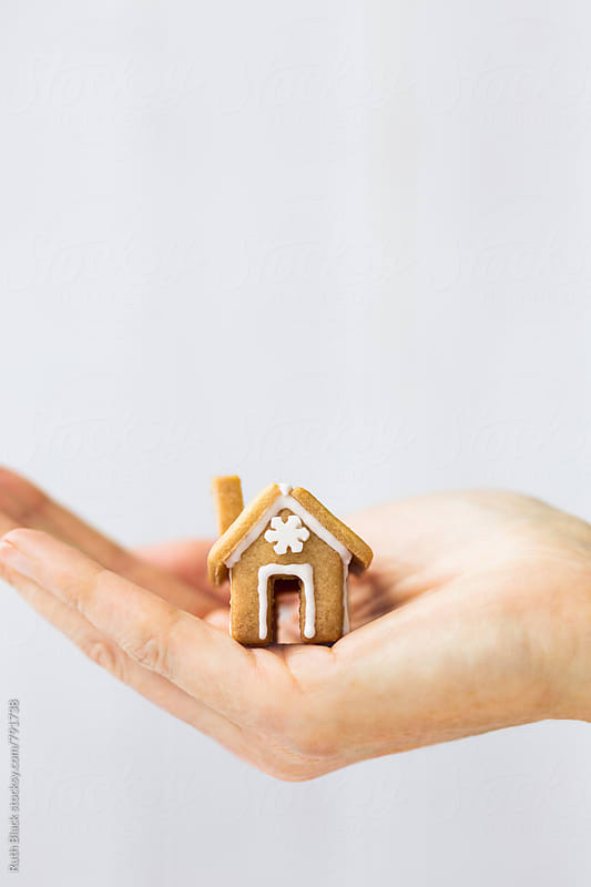Hand holding mini gingerbread house by Ruth Black for Stocksy United