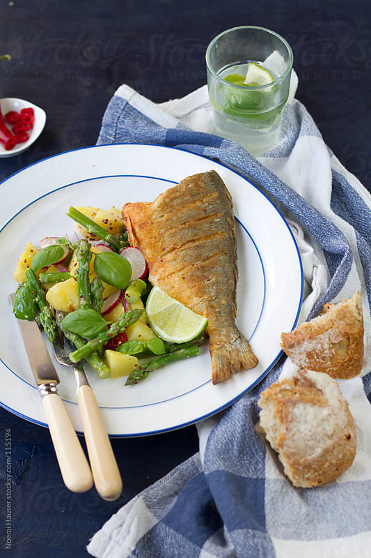 Fried fish with potato and asparagus salad  by Noemi Hauser for Stocksy United