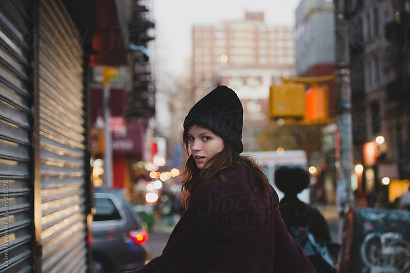 Woman walking down sidewalk in the city by Lauren Naefe for Stocksy United