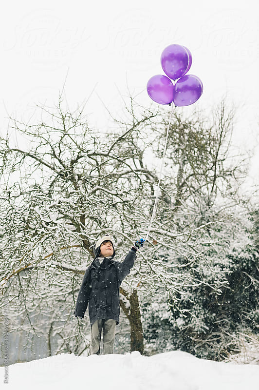 Child in snow holding purple balloons by Rebecca Spencer for Stocksy United