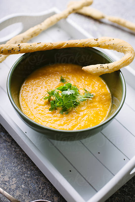 A bowl of healthy homemade carrot soup, served with gluten free bread sticks. by Darren Muir for Stocksy United