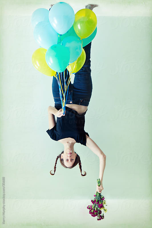 Woman hanging upside down from ceiling with balloons by Kerry Murphy for Stocksy United