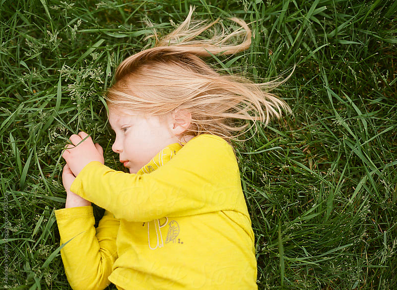 Little Girl in a Yellow Shirt Lays in the grass While Clasping Her Hands by Amanda Voelker for Stocksy United