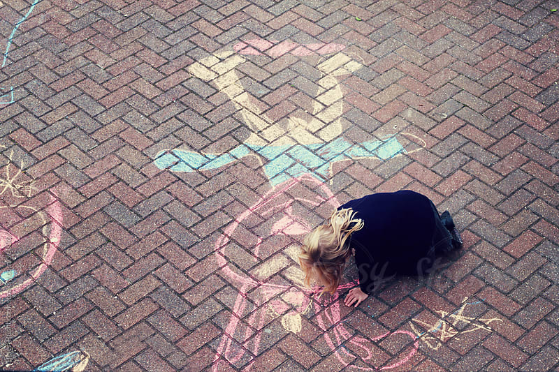 A little girl chalking on a pavement by Helen Rushbrook for Stocksy United