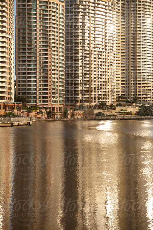 Waterfront apartments reflected in river at sunrise by Ben Ryan for Stocksy United