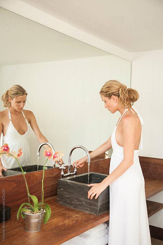 Woman getting ready in modern luxury bathroom  by Trinette Reed for Stocksy United