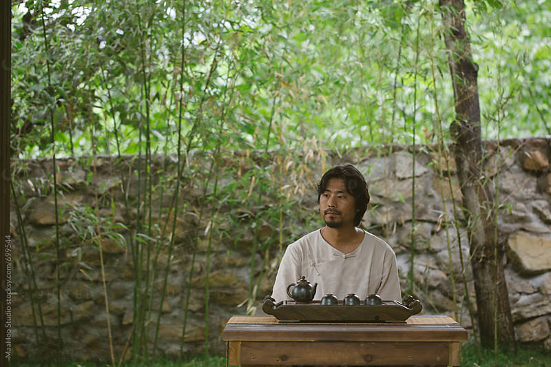 Man wearing traditional Chinese cloth sitting in a garden by MaaHoo Studio for Stocksy United