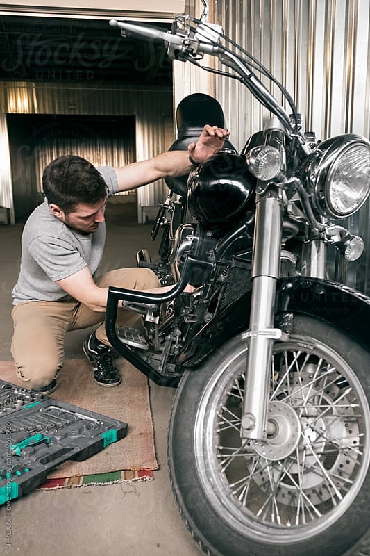 Young man repairing his polished motorbike by Danil Nevsky for Stocksy United