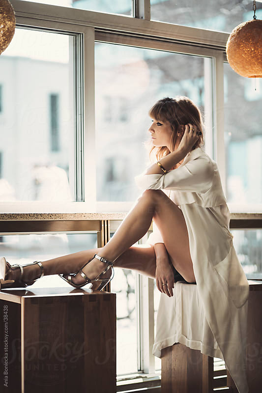 A beautiful model sitting by a counter at a lounge looking out through the window by Ania Boniecka for Stocksy United