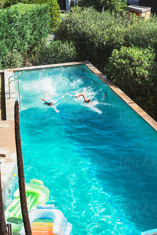 two girls swimming in a backyard pool by Gillian Vann for Stocksy United