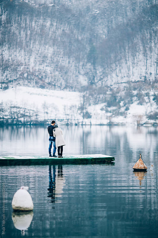 Couple on a lake at winter by Maja Topcagic for Stocksy United