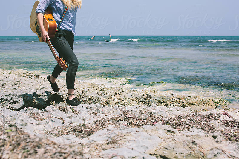 Girl walks along rocks at the beach with her guitar by Jacqui Miller for Stocksy United