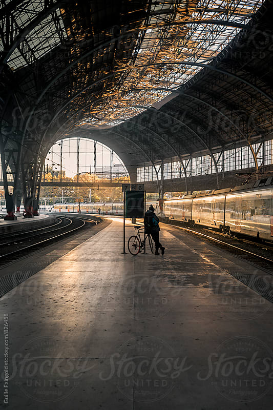 unrecognizable Biker waits patiently in railway station by Guille Faingold for Stocksy United