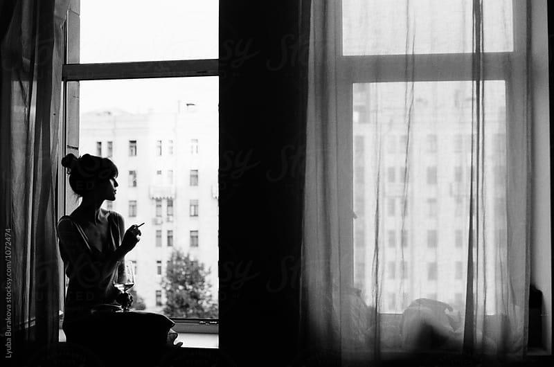 Silhouette of a woman having wine and cigarette by Liubov Burakova for Stocksy United