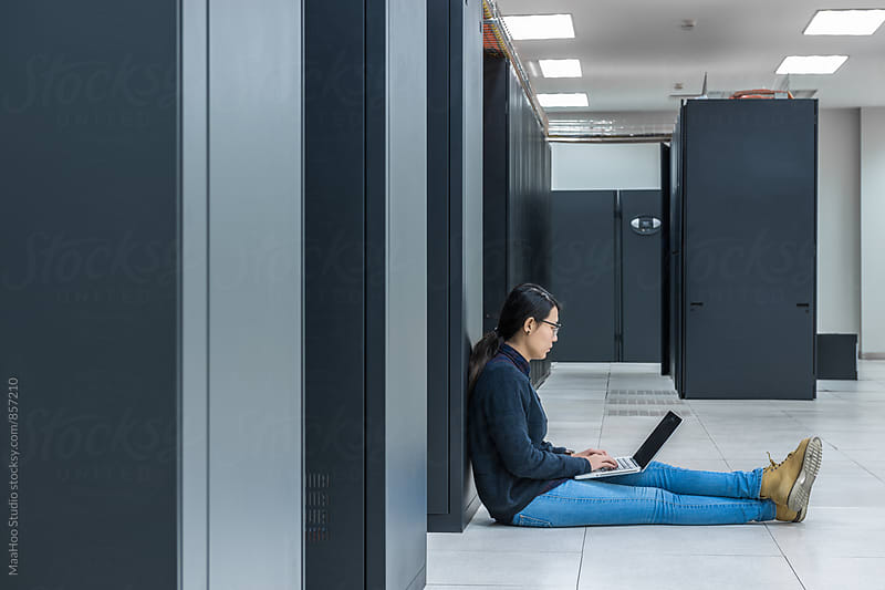 Female engineer using laptop in data center by MaaHoo Studio for Stocksy United