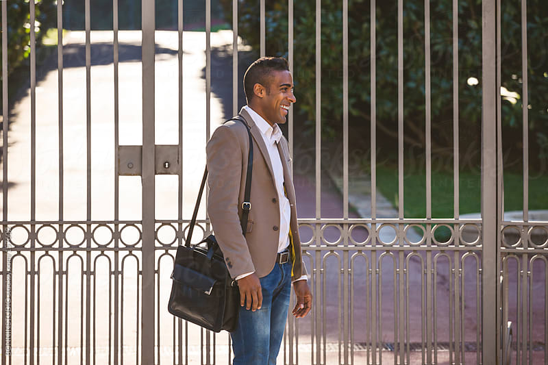 Black businessman smiling in front big gate in the park. by BONNINSTUDIO for Stocksy United