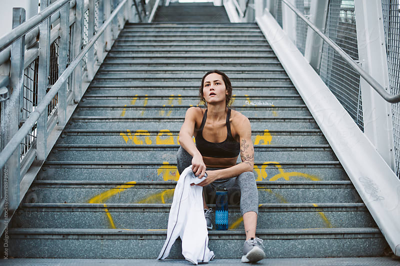 Young woman cooling off on stairs after hard work out by Kate Daigneault for Stocksy United