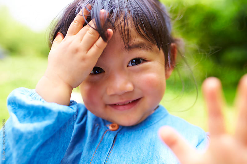 close up of happy little asian girl outdoor by Bo Bo for Stocksy United