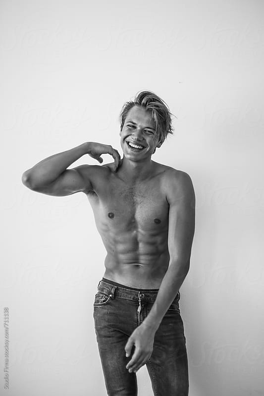 Black and white portrait of a young blonde man shirtless. by Studio Firma for Stocksy United
