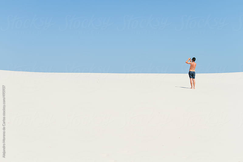 Young man wearing swimsuit taking a photo on idyllic beach by Alejandro Moreno de Carlos for Stocksy United