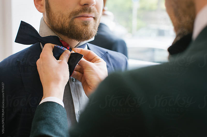 Men's Fashion - Close Up of Man Helping Friend to Tie Bow Tie by VISUALSPECTRUM for Stocksy United