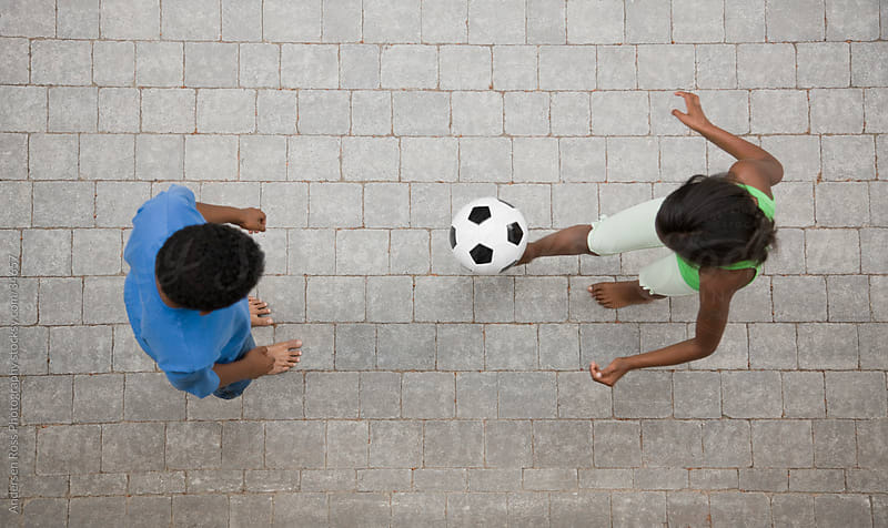 Boy (10-11) and girl (8-9) playing ball outdoors by Andersen Ross Photography for Stocksy United