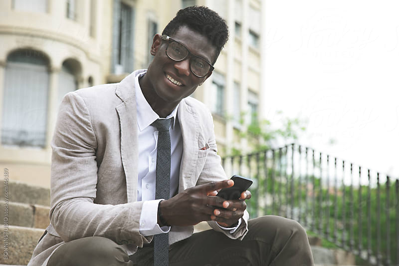 Smiling african young businessman with rimmed glasses sending a message on smartphone by BONNINSTUDIO for Stocksy United