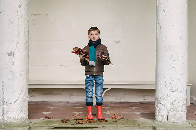 Child with both hands full of autumn leaves by Rebecca Spencer for Stocksy United