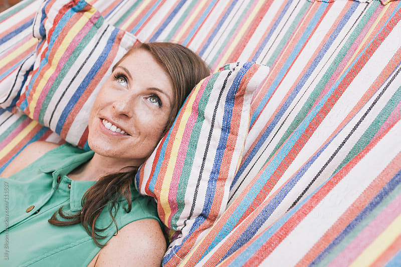Young woman daydreaming in a hammock by Lilly Bloom for Stocksy United