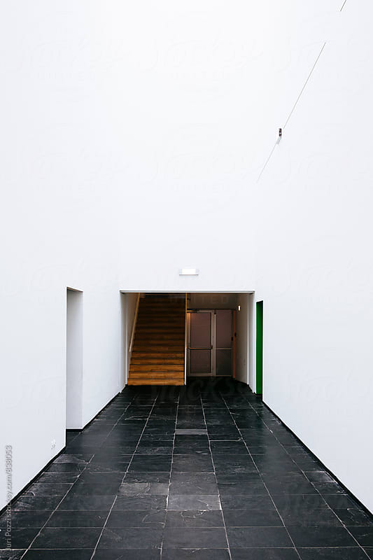 white corridor paved with black stones by Juri Pozzi for Stocksy United