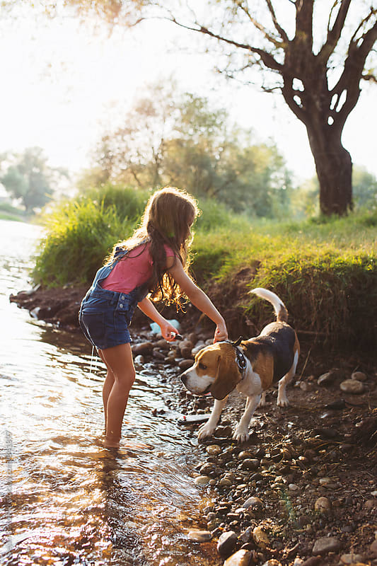 Girl and her pet refresh in river. by Dejan Ristovski for Stocksy United