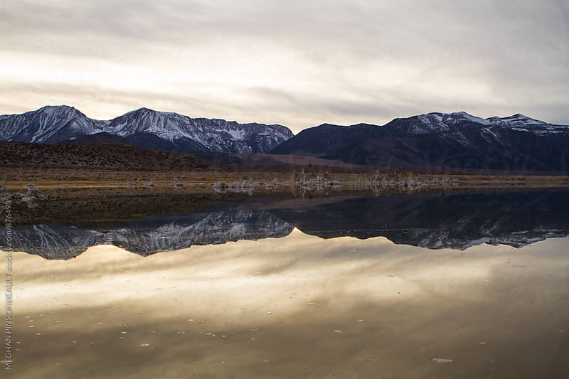 Snowy Mountains Reflecting on Winter Lake at Dusk by Meg Pinsonneault for Stocksy United