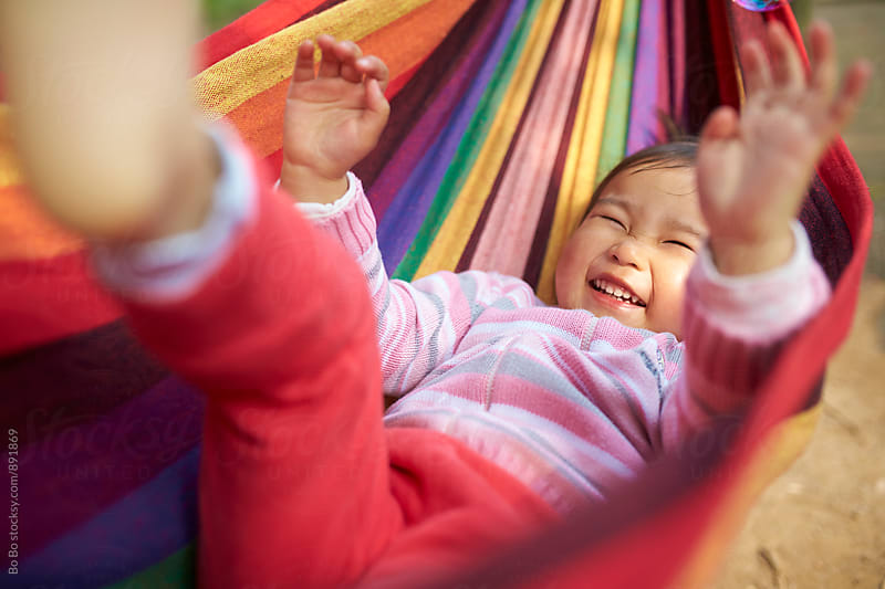 happy little asian girl slepping in the hammock by Bo Bo for Stocksy United