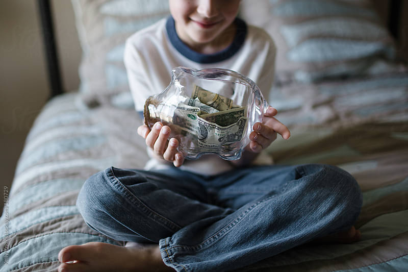 boy holding a piggy bank by Kelly Knox for Stocksy United
