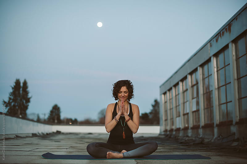 woman sits on roof of urban building in yoga prayer pose at dusk. by Kate Daigneault for Stocksy United